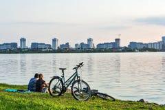 Mann und Frau, die auf dem Ufer und dem Blick an der Stadt sitzen Lizenzfreie Stockfotografie