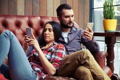 Mann und Frau, die auf der Couch sich entspannen lizenzfreies stockfoto