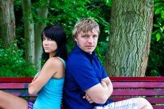 Mann und Frau, die auf der Parkbank sitzen Stockfoto