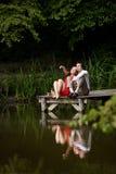 Mann und Frau, die auf einem hölzernen Pier auf dem See küssen Stockfotografie