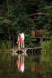 Mann und Frau, die auf einem hölzernen Pier auf dem See küssen Lizenzfreie Stockfotografie