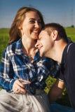 Mann und Frau, die auf einem Picknick lachen Stockfotos
