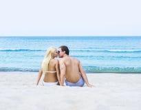 Mann und Frau, die auf einem Sommerstrand sitzen und küssen Stockfoto