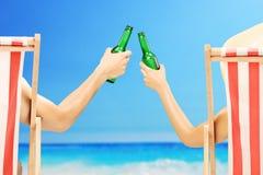 Mann und Frau, die auf einem Strand sich entspannen und mit Bier zujubeln lizenzfreie stockbilder
