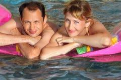 Mann und Frau, die auf einer Matratze im Pool liegen Stockbilder
