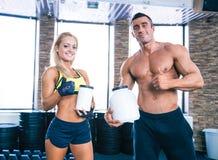 Mann und Frau, die Behälter mit Sportnahrung halten Stockfoto