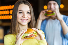 Mann und Frau, die Burger essen Junges Mädchen und junger Mann halten Burger auf Händen lizenzfreie stockfotografie