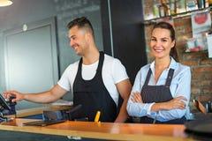 Mann und Frau, die am Café arbeiten Stockbild