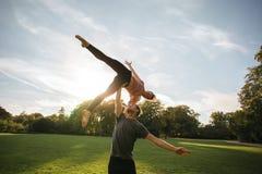 Mann und Frau, die das Paaryoga im Freien in einem Park tut Lizenzfreie Stockfotos