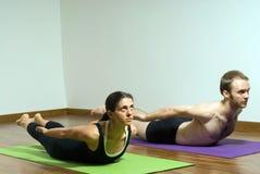 Mann und Frau, die das Yoga - horizontal durchführt Stockfotografie
