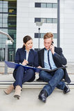 Mann und Frau, die an Dateien vor Büro arbeiten Stockbild