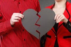 Mann und Frau, die defektes Herz halten Stockfoto