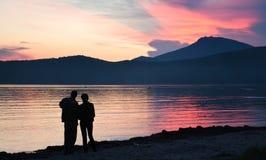 Mann und Frau, die den Sonnenuntergang betrachten Lizenzfreie Stockfotografie