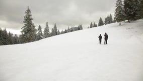 Mann und Frau, die in den Winterbergen wandern stock footage