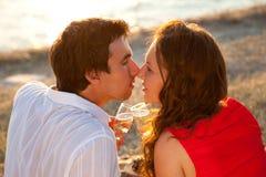 Mann und Frau, die in der Hand mit Gläsern Champagner küssen Lizenzfreie Stockfotos