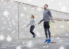 Mann und Frau, die draußen mit Seilspringen trainieren Stockfotografie