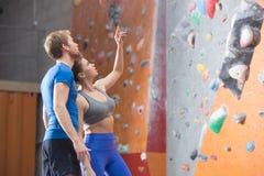 Mann und Frau, die durch Kletterwand in crossfit Turnhalle sich besprechen Lizenzfreies Stockbild