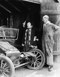 Mann und Frau, die ein ruiniertes Auto in der Scheune betrachten (alle dargestellten Personen sind nicht längeres lebendes und ke Stockbilder