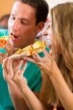 Mann und Frau, die eine Pizza essen Lizenzfreies Stockfoto