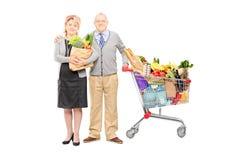 Mann und Frau, die eine Tasche und einen Warenkorb voll von den Lebensmittelgeschäften hält Stockfotos