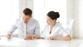 Mann und Frau, die einen Vertrag unterzeichnen stock footage