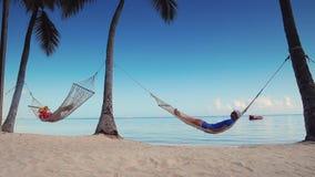 Mann und Frau, die in einer Hängematte auf Tropeninselstrand sich entspannen stock video