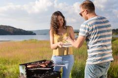 Mann und Frau, die Grill am Seeufer in der Natur haben Lizenzfreie Stockfotografie