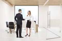 Mann und Frau, die Hände in der Chefetage mit quadratischem Fenster rütteln Lizenzfreies Stockfoto
