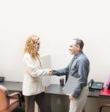 Mann und Frau, die Hände im Büro rütteln Lizenzfreie Stockbilder