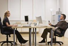Mann und Frau, die im Büro plaudern Stockfotografie