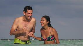 Mann und Frau, die im Ozean lachen stock footage