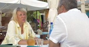 Mann und Frau, die im Restaurant, in der Unterhaltung und im Lachen sitzen stock footage