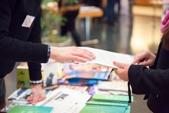 Mann und Frau, die Informations-Broschüre über Ausstellungs-Stand teilen stockfotos