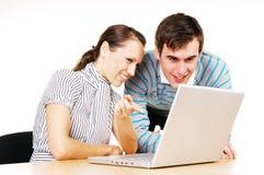 Mann und Frau, die innen zum Überwachungsgerät des Laptops schauen Stockfotografie