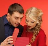 Mann und Frau, die innerhalb der Geschenkbox schauen Lizenzfreie Stockfotos