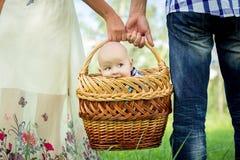 Mann und Frau, die Korb mit kleinem Jungen halten Stockfotografie