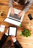Mann und Frau, die an Laptop und Tablette arbeiten Stockfotografie
