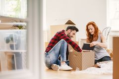 Mann und Frau, die Material nach Verlegung zum neuen Haus auspacken lizenzfreies stockbild