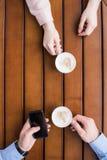 Mann und Frau, die mit Tasse Kaffees und dem Mann verwendet Smartphone sitzt Stockfotos