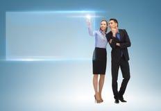 Mann und Frau, die mit virtuellem Schirm arbeiten stockbild