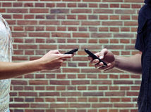 Mann und Frau, die Mobiltelefone verwendet, um Dateien zu teilen Lizenzfreie Stockfotografie