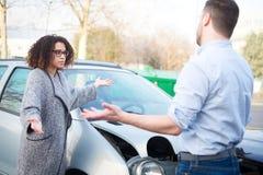 Mann und Frau, die nach schlechtem Autounfall argumentieren stockbilder