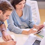 Mann und Frau, die nah bei der Arbeit im Büro zusammenarbeiten Lizenzfreie Stockfotos