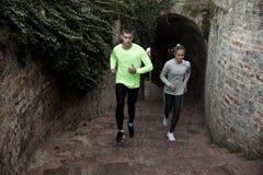 Mann und Frau, die oben zusammen laufen Stockfotografie