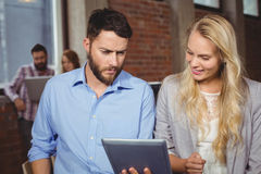 Mann und Frau, die in Richtung der digitalen Tablette blicken Lizenzfreie Stockbilder