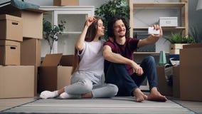 Mann und Frau, die selfie mit Schlüsseln zur neuen Wohnung nach Verlegung nehmen stock footage