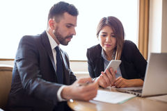 Mann und Frau, die Smartphone in der Sitzung verwendet stockfotografie