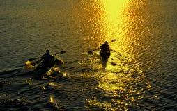 Mann und Frau, die am Sonnenuntergang Kayaking sind Stockbild