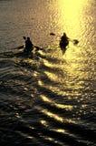 Mann und Frau, die am Sonnenuntergang Kayaking sind Stockfoto