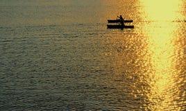Mann und Frau, die am Sonnenuntergang Kayaking sind Stockbilder